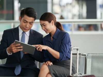 asian couple using tablet airport